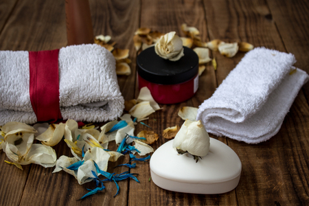 a soap and different skin creams with towels and flowers on wooden background