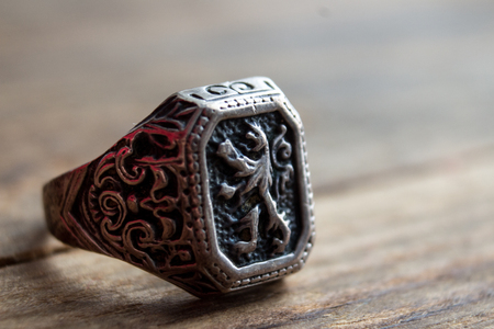 ring with a lion coat of arms on a wooden background