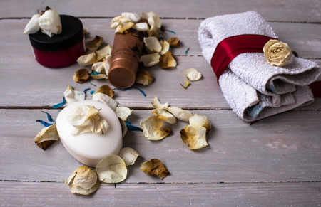 a soap and different skin creams with towels and flowers on grey wooden background