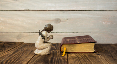 the angel and bible on a wooden background Stock Photo