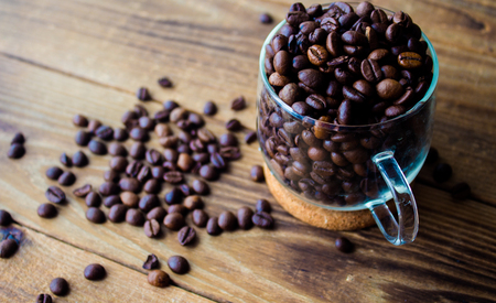 a cup of coffe beans on wooden background Stock Photo