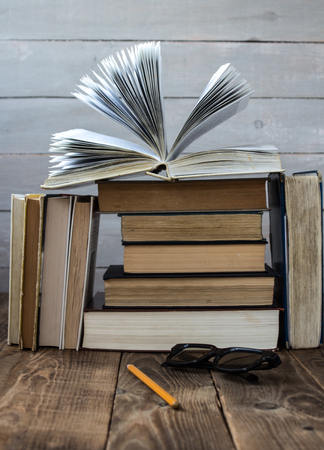 open book on a pile of books on wooden background