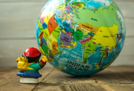 a toy and the globe on wooden bsckground