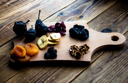 prunes and dried apricots raisins cranberries on wooden background