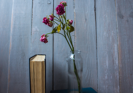 roses in a bottle and a book on wooden background