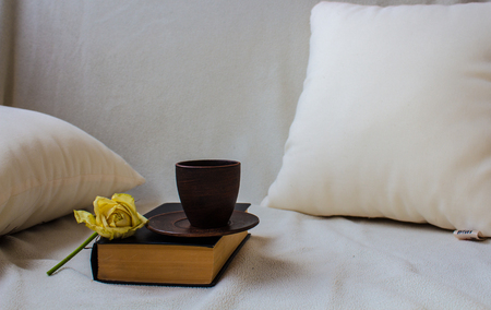 a cup on the book with rose o