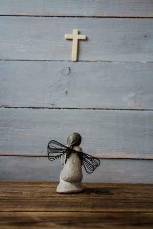 a angel and cross on wooden background