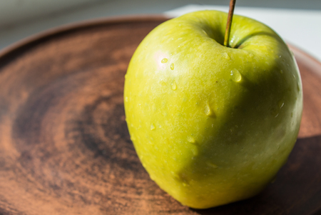 a green apple on a plate in the sun
