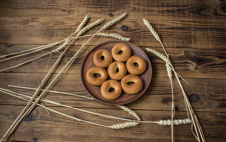 bagels in a plate with spikelets on wooden background Stock Photo
