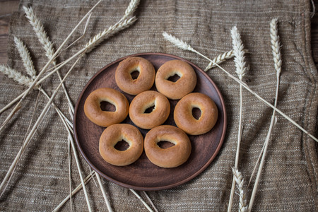 bagels in a plate with spikelets on sackcloth background