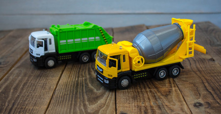 Toy garbage truck and concrete mixer on wooden background
