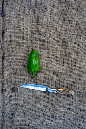 bell pepper and knife on sacktloth background
