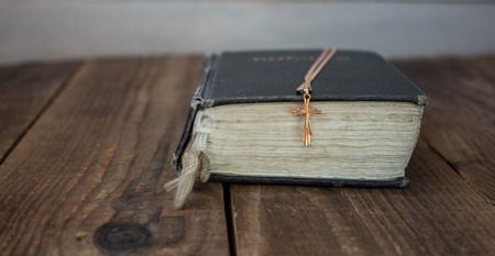 golden cross on a bible on wooden background