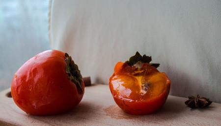 a ripe persimmon with onyx and cinnamon on wooden deck Archivio Fotografico
