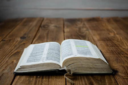 a open old bible on wooden background