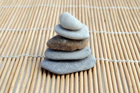 zen stones on bamboo background. concept of meditation, armony, relax and wellness