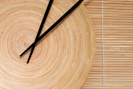 japanese chopsticks in wooden round dish on bamboo placemat background  Stock Photo - 10029285