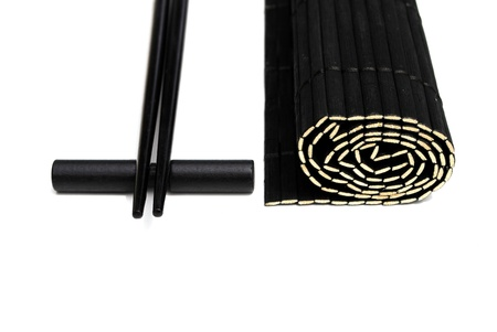 black chopsticks and black bamboo placemat on white background Stock Photo - 10029273