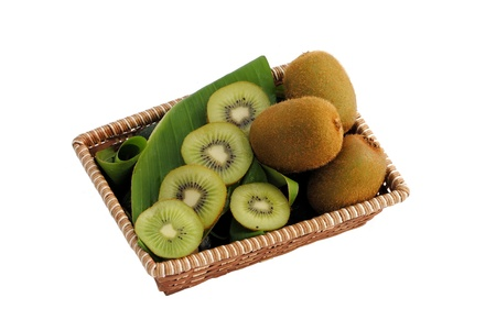 whole and sliced kiwi in a straw basket Stock Photo - 10183237