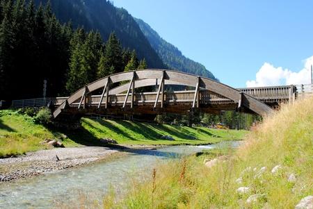 wooden bridge over river in mountain landscape Stock Photo