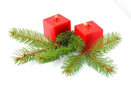 candele rosse e aghi di pino verde su sfondo bianco