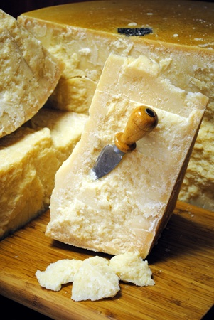 Italian parmesan cheese with knife on wooden cutting board photo