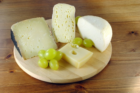 Italian cheese with grapes on wooden cutting board photo