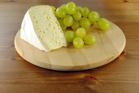 Italian cheese with grapes on wooden cutting board Stock Photo
