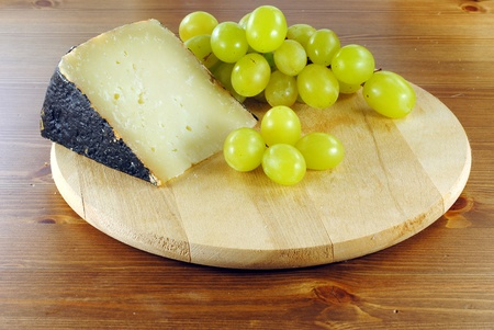 Italian cheese with grapes on wooden cutting board, make with sheep milk photo