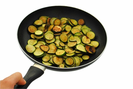 cooked courgettes with rosemary in frying pan on white background