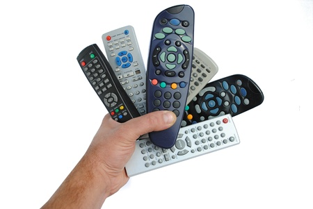 universal: man hand holds six remote control, isolated on white background Stock Photo