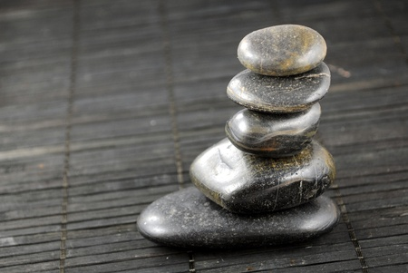 black zen stones on bamboo place mat, concept of balance