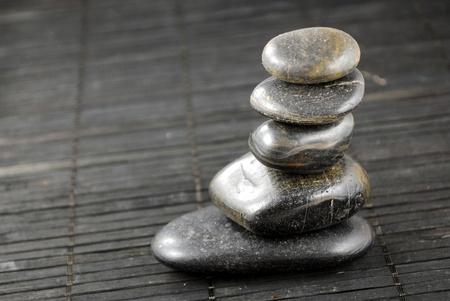pietre nere zen sulla tovaglietta di bamb�, concetto di equilibrio Archivio Fotografico