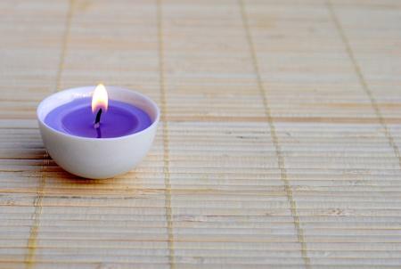 illuminato candela viola sulla tovaglietta di bamb� Archivio Fotografico