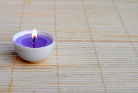 lighted purple candle on bamboo place mat
