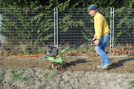 Middle age man with a rototiller in the garden photo