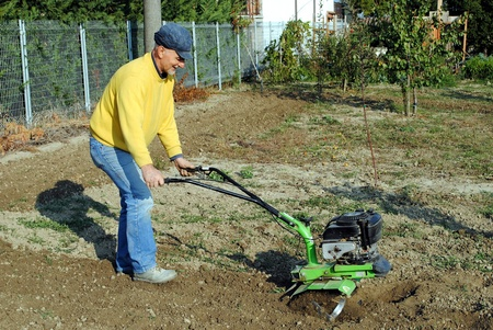 Uomo di mezza et� con un rototiller in giardino