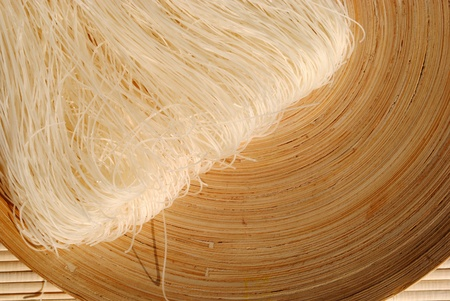 raw rice needles on a round wooden dish  Stock Photo