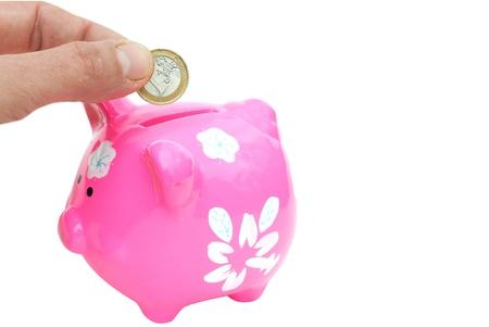 fingers put an Euro coin in a piggy bank Stock Photo - 13335616