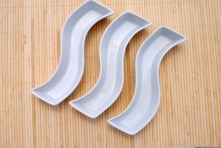placemat: three white dishes over a bamboo placemat Stock Photo