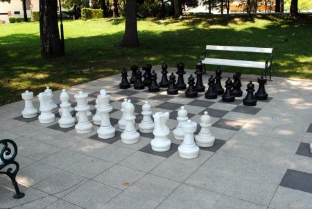 scacchi grande situato nel parco con panchine Archivio Fotografico