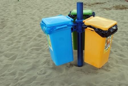 colorati bidoni della spazzatura, sulla spiaggia di sabbia Archivio Fotografico