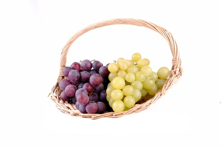 red and green grapes in a straw basket, isolated on white Stock Photo