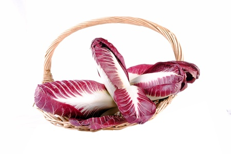 red radicchio salad in a straw basket, isolated on white photo