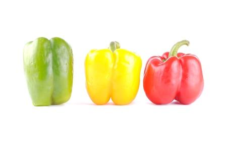 tre peperoni colorati su bianco, le ombre morbide
