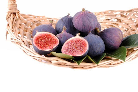 purple figs in a straw basket, isolated on white Stock Photo