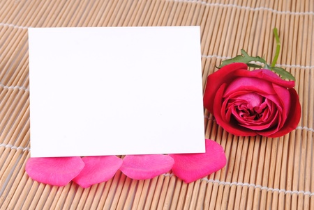 rose and a blank card on a bamboo place mat photo