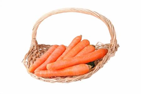 carote organiche in un cesto di paglia, isolato su bianco