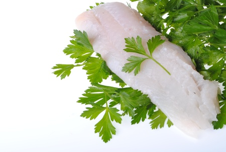 cod steak over parsley isolated on white background