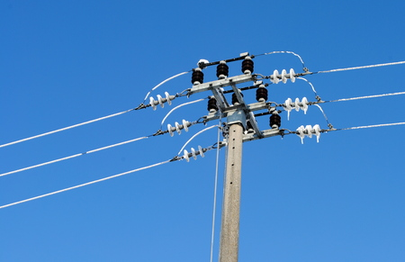 utility pole with electric frozen wires and cables